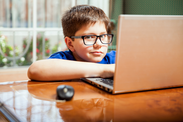 bigstock-Kid-Doing-Homework-On-A-Laptop-84634460